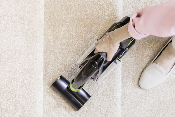 Woman cleaning kitchen surface with Gtech Multi vacuum cleaner