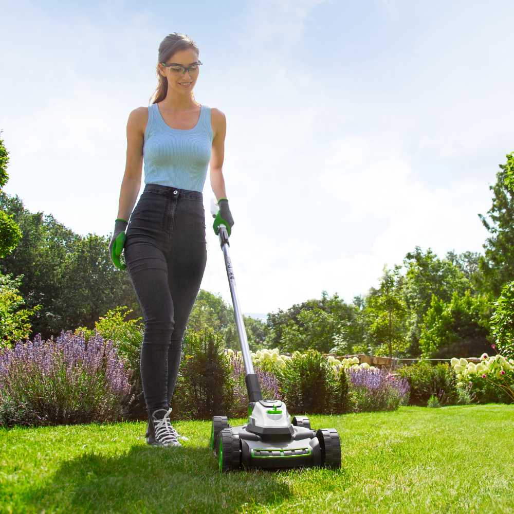 Woman using small lawnmower on sunny day
