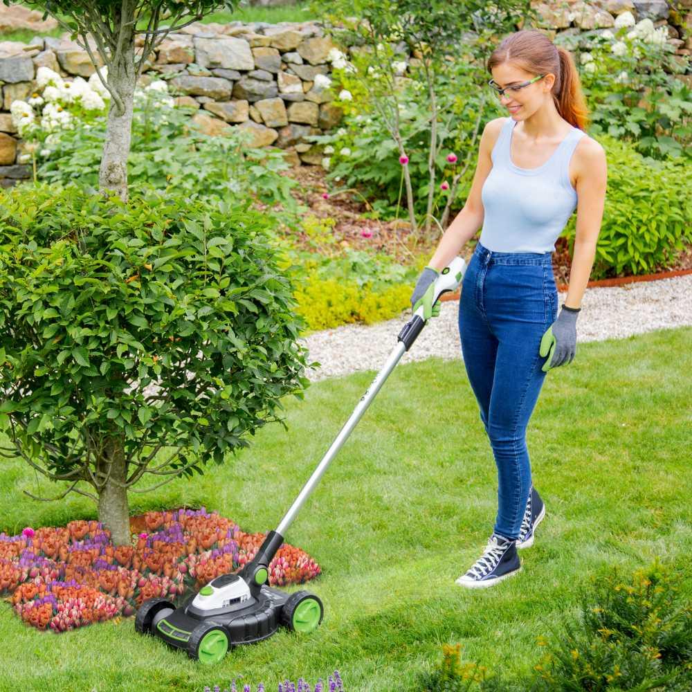 Lightweight lawn mower cutting next to flower bed