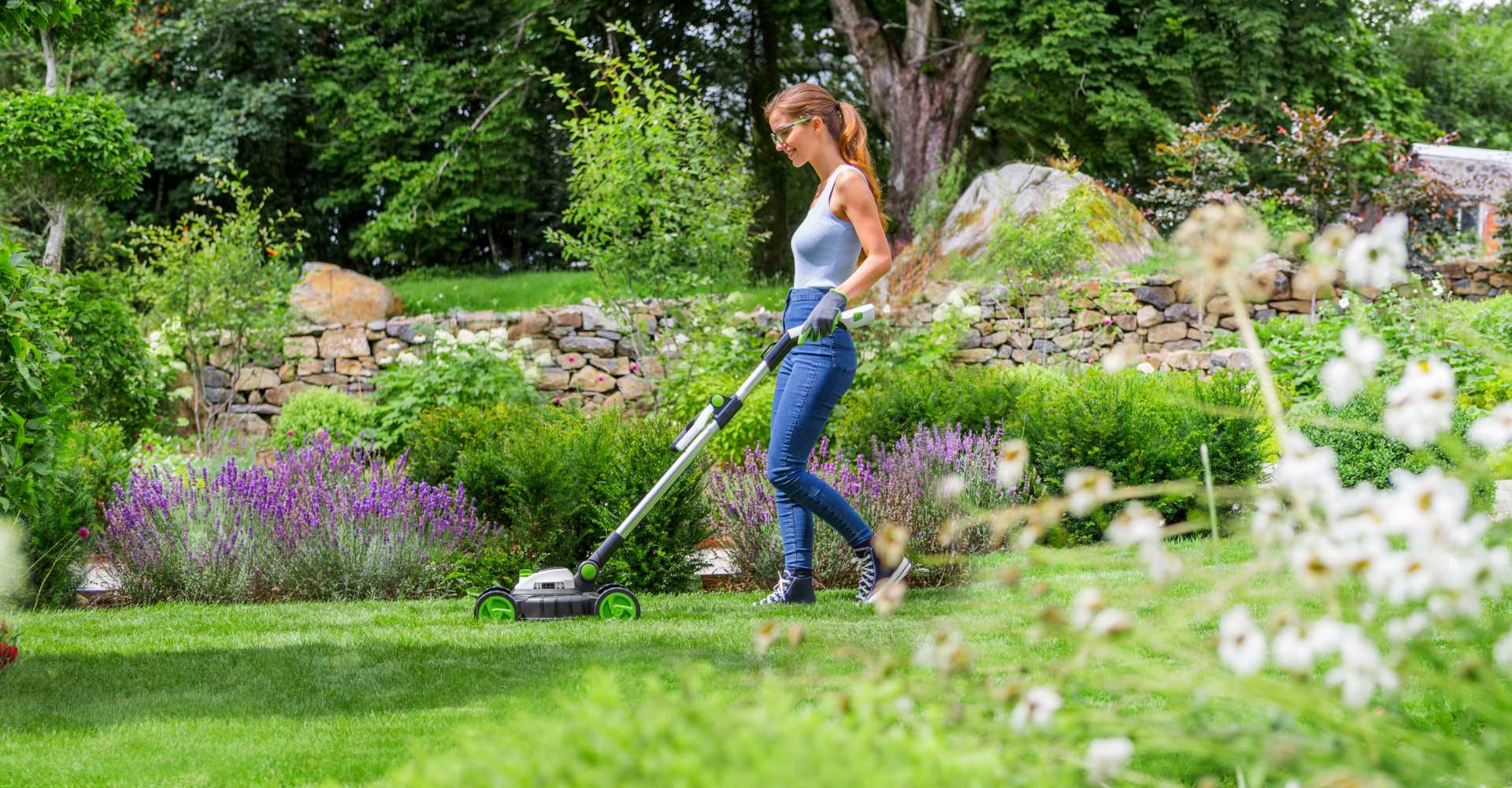 Small electric lawn mower being used by woman in garden