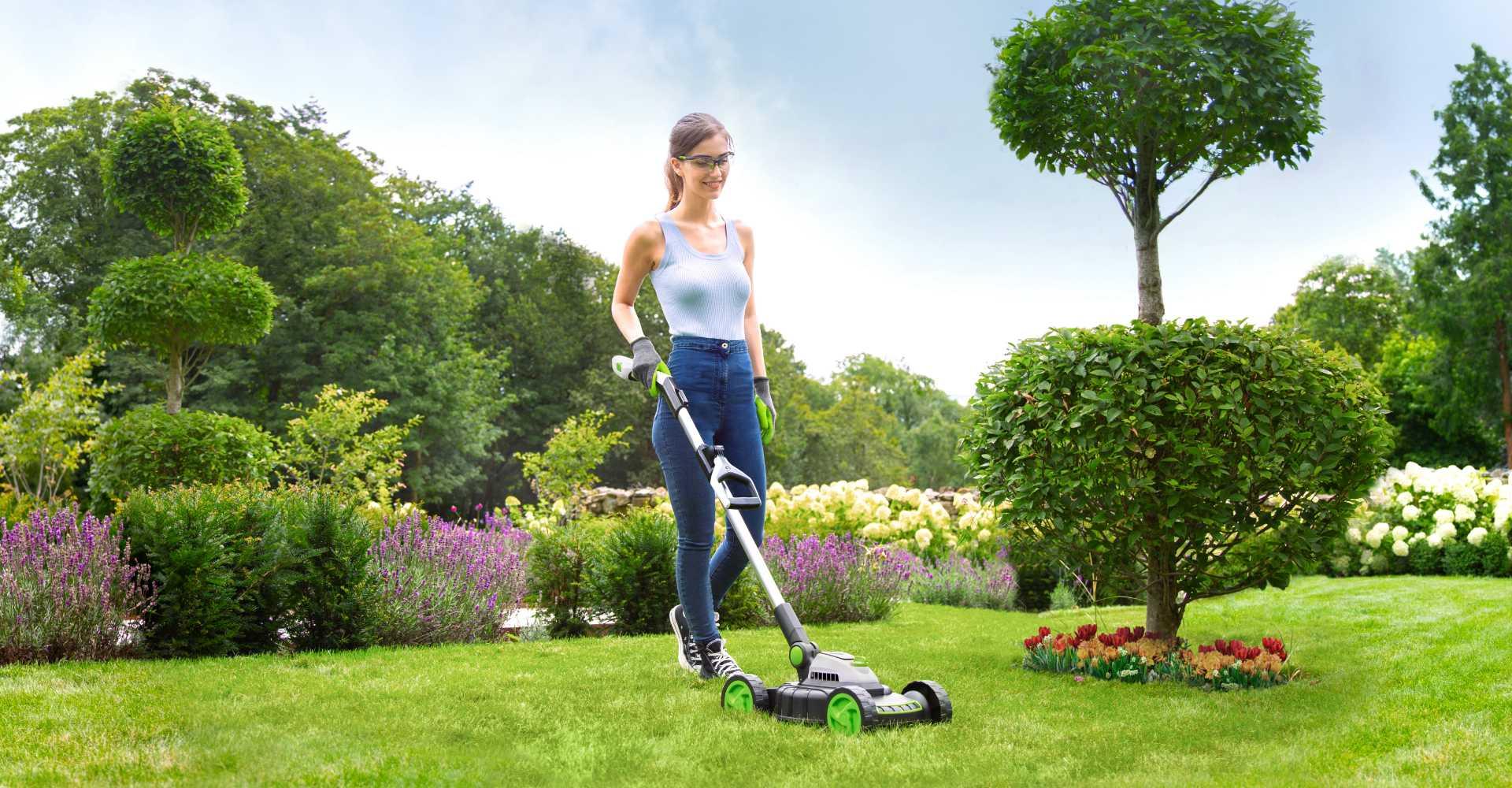 Woman using mini lawnmower in garden