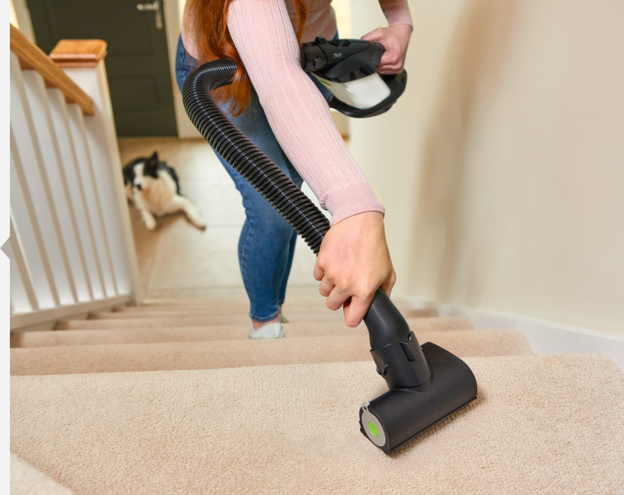 Woman using ProLite handheld vacuum with flexible hose attachment to vacuum stairs