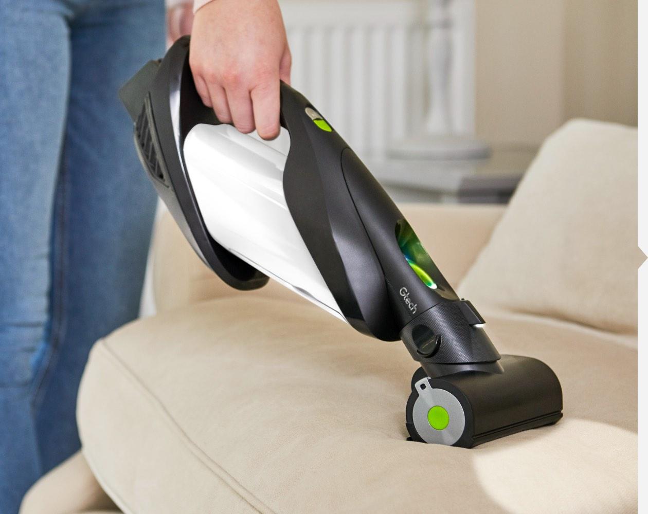 Woman using ProLite handheld vacuum with power head attachment to vacuum sofa